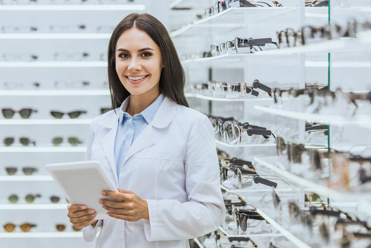 beautiful smiling optician using digital tablet near shelves with eyeglasses in ophthalmic shop