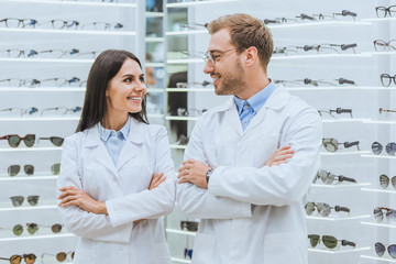 professional smiling doctors posing with crossed arms in ophthalmic shop with eyeglasses