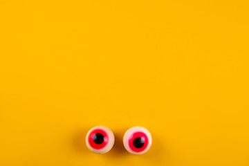 Eyeball shaped candies with red pupils on bright yellow background. Halloween decor concept. Copy space, close up, top view, flat lay.