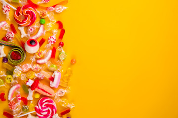 Assorted teeth & eyeball shaped candy spread on yellow background, jelly spider, gummy worms, sugar bones, round lollipop and other mixed candy, bloody finger. Top view, copy space, close up, flat lay