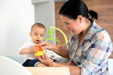 Mother showing her infant how to assemble a toy