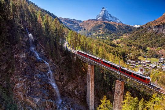 Zermatt, Switzerland. Image of Swiss Alps with Gornergrad tourist train, waterfall and Matterhorn in Valais region.