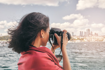 Wall Mural - Woman photographer with red scarf, taking pictures of landscape at sea