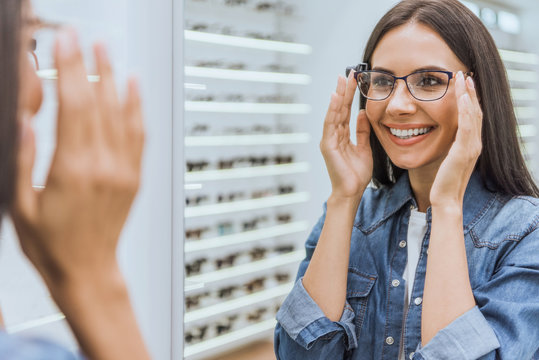 partial view of smiling woman choosing eyeglasses and looking at mirror in optica