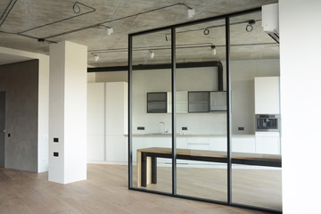 Modern room after remodeling and renovating with contemporery glass wall and loft kitchen interior design.
