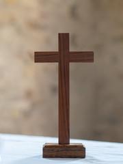 Wooden cross on white altar cloth background. Christian faith.