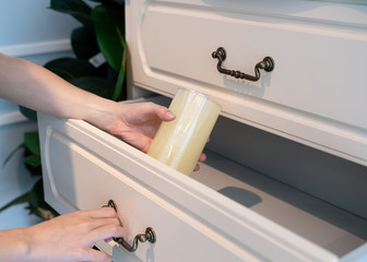 Hand Pull Open white Wooden Drawer. White aroma candle in hand.