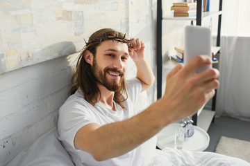 high angle view of Jesus in crown of thorns taking selfie in bed during morning time at home