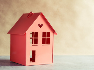 Metal red model of a house with a heart. The concept of home and domestic life. Copy space.