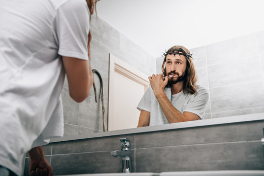 partial view of Jesus with towel over shoulder brushing teeth and looking at own reflection in bathroom