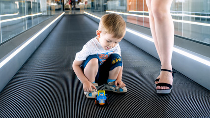 2 years old toddler boy playing with toys on moving walkway at airport terminal