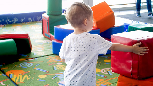 Cute toddler boy playing on indoor playground with soft blocks