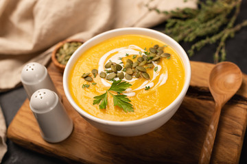 Pumpkin cream soup in bowl decorated with cream, pumpkin seeds and thyme. Selective focus