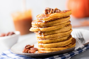 Tasty pumpkin pancakes with caramel sauce and nuts. Selective focus. Autumn comfort food, american Thanksgiving day breakfast