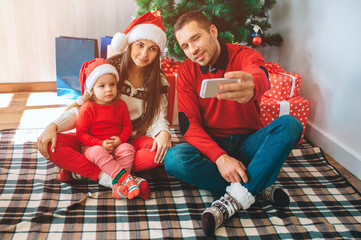 Merry Christmas and Happy New Year. Young man sits besides woman and child. He holds phone and takes selfie. Woman and kid lok at it and pose. Family wears Christmas clothes and hats.