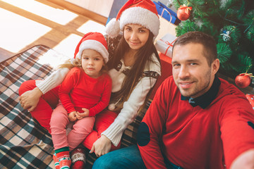 Merry Christmas and Happy New Year. Picture of nice family. Young man hold camera and takes selfie. All of them pose. Kid looks serious. They sit at Christmas tree on blanket.