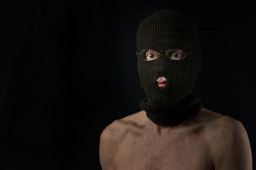 portrait of senior retired robber wearing only a balaclava on black background