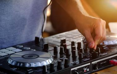 DJ plays and mix music on digital midi controller.