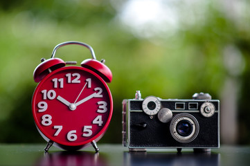Red clock and camera Put on the table Time and shooting equipment Concepts of punctuality and photography
