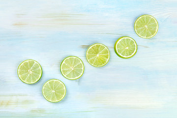 An overhead photo of many vibrant lime slices on a teal blue background