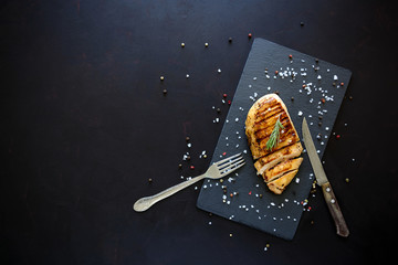 Grilled chicken fillets on slate plate with rosemary and spices on dark wooden background. Top view. Flat lay. Copy space