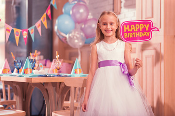 Birthday sign. Positive relaxed girl smiling happily while standing with happy birthday sign in her hands
