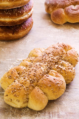 Close-up of bread braid with sesame seeds on wooden background.