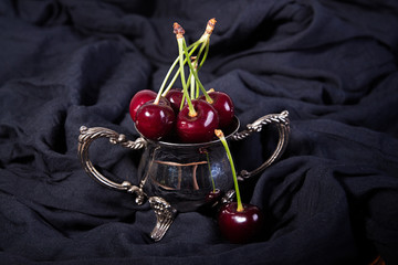Ripe sweet cherries in small metall bowl on blak fabric.