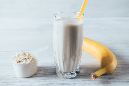 Glass of sports shake next to ripe banana and dry powder
