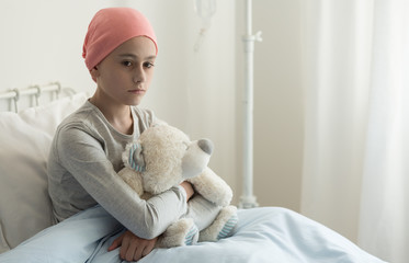 Sad sick girl with pink headscarf hugging plush toy in the hospital