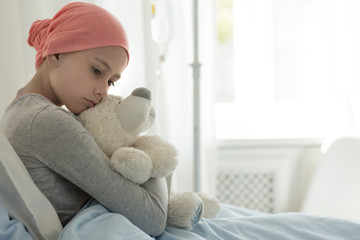 Weak girl with cancer wearing pink headscarf and hugging teddy bear