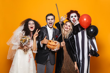 Group of cheerful friends dressed in scary costumes c