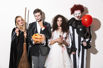 Group of cheerful friends dressed in scary costumes