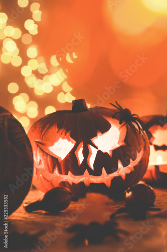 Vertical view of scary orange halloween pumpkin on the table, real photo with copy space