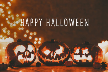 Caption Happy Halloween on the photo of three creepy pumpkins lanterns carved for halloween