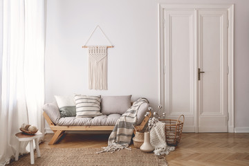 Pillows and blanket on wooden sofa in white loft interior with door and table on carpet. Real photo