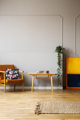 Wooden table between armchair and painting in grey apartment interior with plant and rug. Real photo
