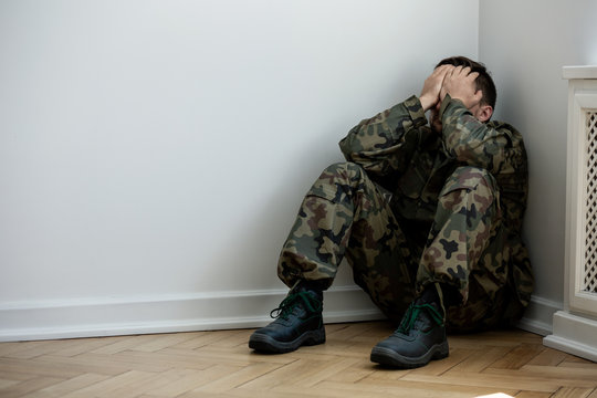 Tired and depressed soldier with war syndrome alone at home. Copy space on the wall