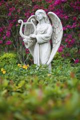 White marble statue of angel in flower garden