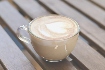 Cup of cappuccino on a wooden table.