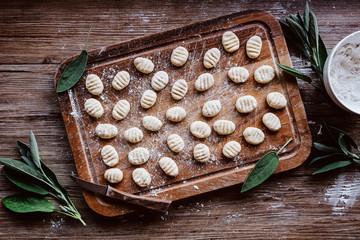 Rohe Gnocchi mit frischem Salbei auf rustikalem Holz