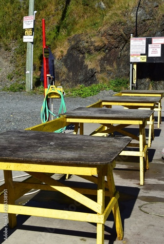 Wooden Tables Used For Outdoor Fish Cleaning Station And Water Hose In A Small Fishing Community