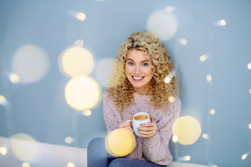Portrait young curly blond woman enjoying coca or caffee hot drink, looking at camera while sitting on the floor on gray blue wall background with bokeh garland abstract lights.