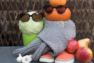 Funny image of autumn harvest: fashionable vegetables wear glasses, scarf and shoes. Concept: happy Halloween garden story.
