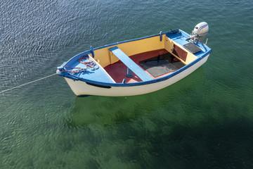 Bateau en bois avec moteur sur l'eau de mer transparente