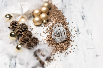 golden and white christmas balls and white feathers on wooden white background