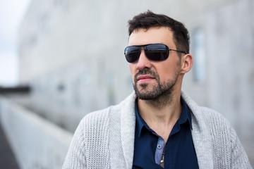 close up portrait of handsome business man over modern building