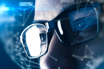 The double exposure image of the businessman wear a smart glasses overlay with futuristic hologram. The concept of modern life, technology, iris scanner and internet of things