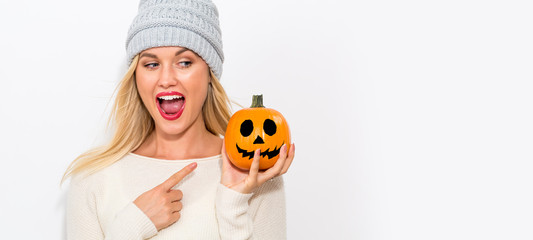 Young woman holding a pumpkin on a white background