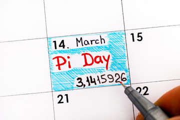 Woman fingers with pen writing reminder Pi Day in calendar.